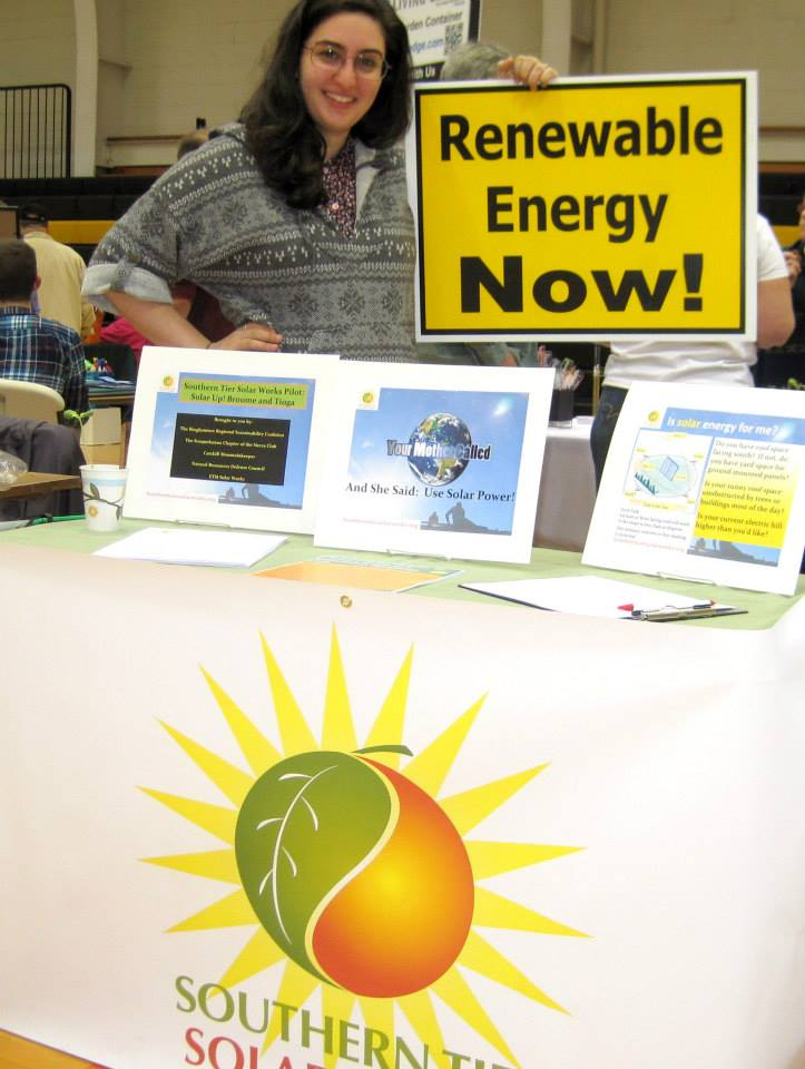 """A table filled with information about solar power staffed by a friendly person holding up a sign that reads """"renewable energy now!"""""""