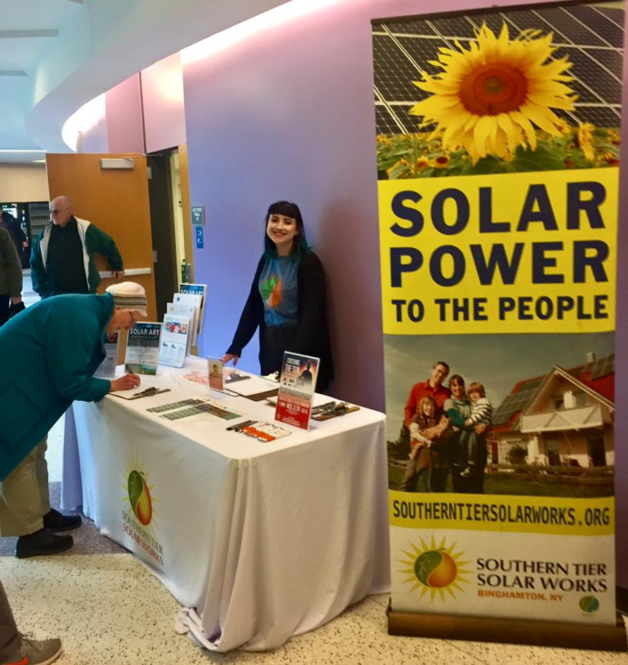 A smiling person standing behind a table filled with information about solar power and a person filling out a sheet on a clipboard